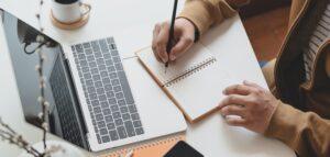 man taking notes near laptop
