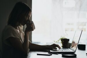 woman watching webinar with a cup of tea